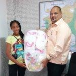 Dirigente comunitario Amaury Peña entrega canastilla a joven embarazada  residente barrio Bienvenido